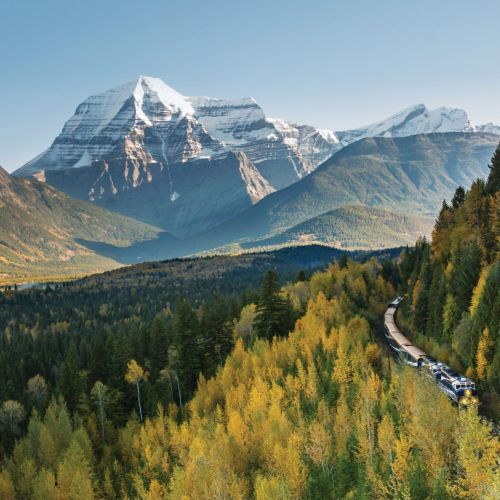 Mount Robson in distance on sunny day, with train wrapping through evergreen trees