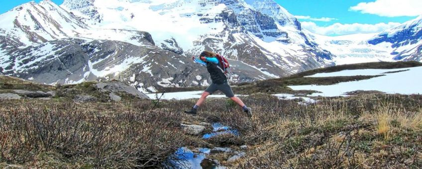Person jumping creek. Icefields tour