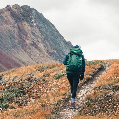 Backpacker walking on a trail near a mountain in Jasper National Park
