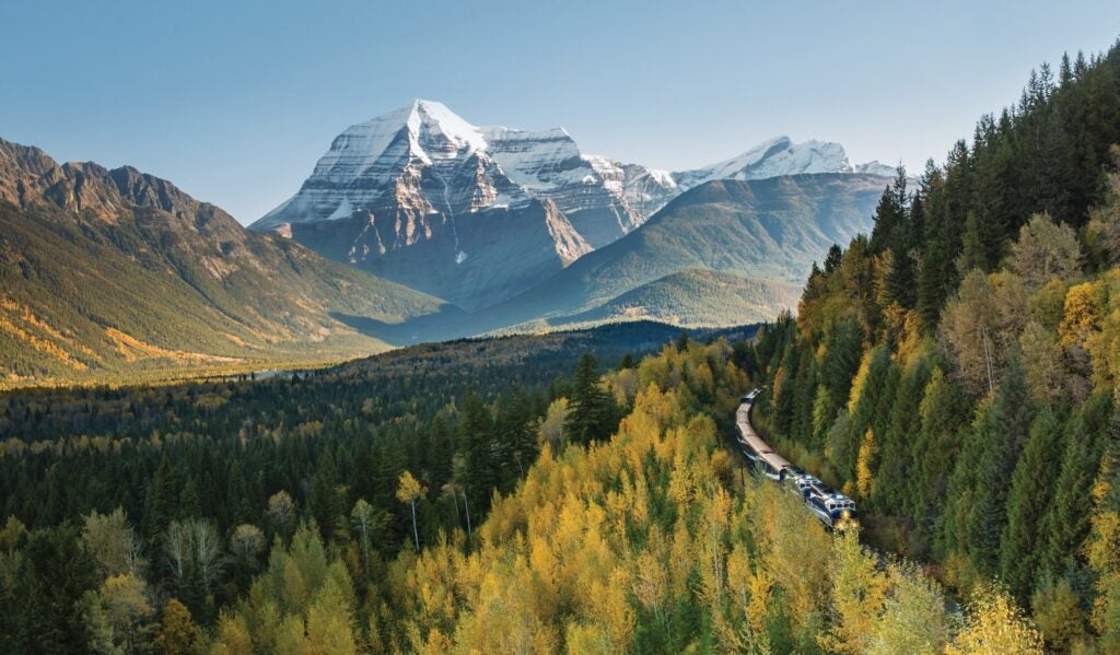 Mount Robson in distance on sunny day, with Jasper Train Tour train travelling through evergreen trees