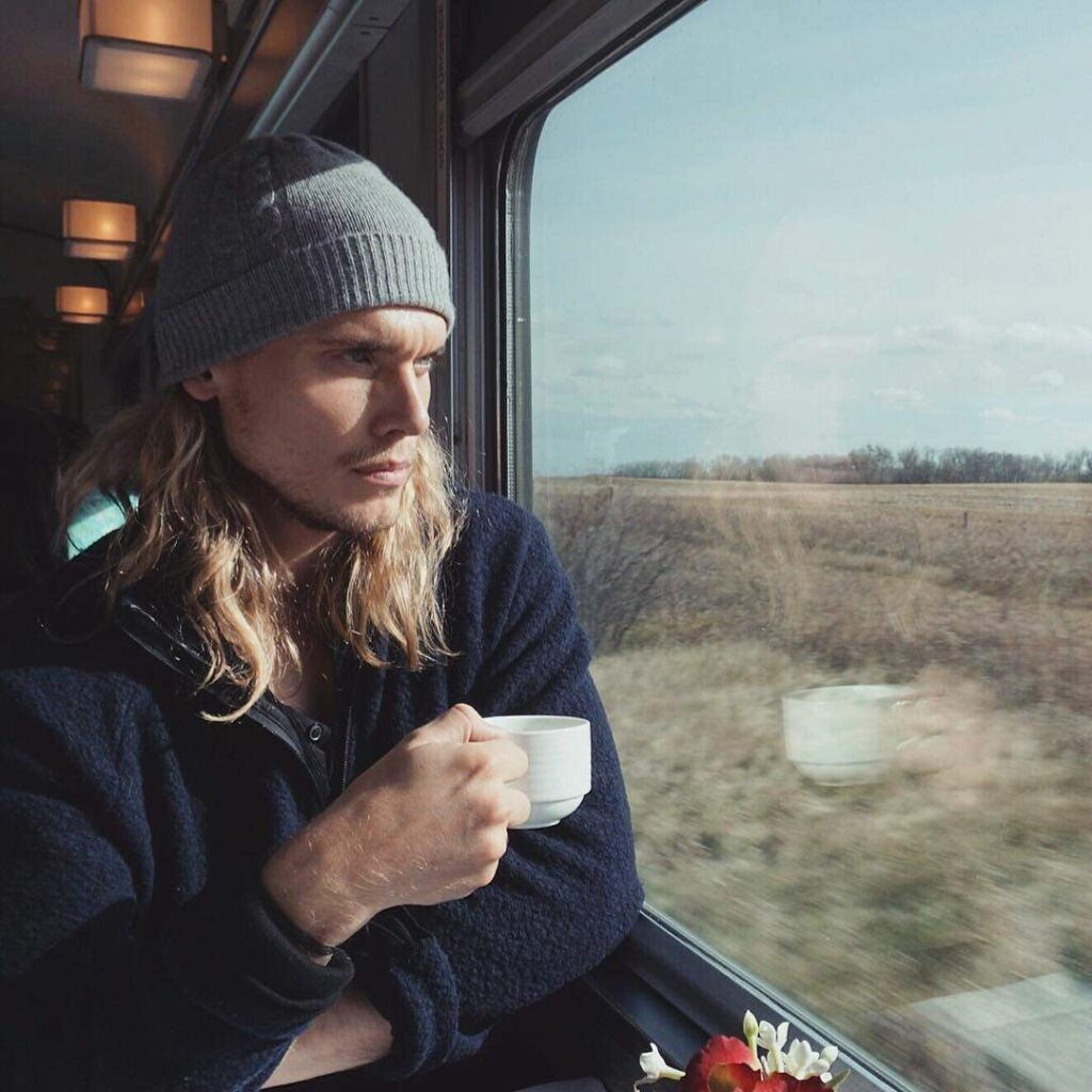A young adult male seated inside the train, he is looking outside through a window while he is holding a cup of coffee.