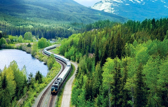 Jasper Train Tour passing by a lake with a forest surrounding it and the Canadian Rockies in the background