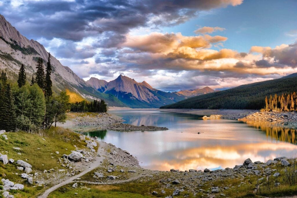 A lake that reflects the sky, the sky is blue and has clouds have on its right side has orange tone from the sun. Behind the lake there are grey coloured mountains that are close to the clouds.
