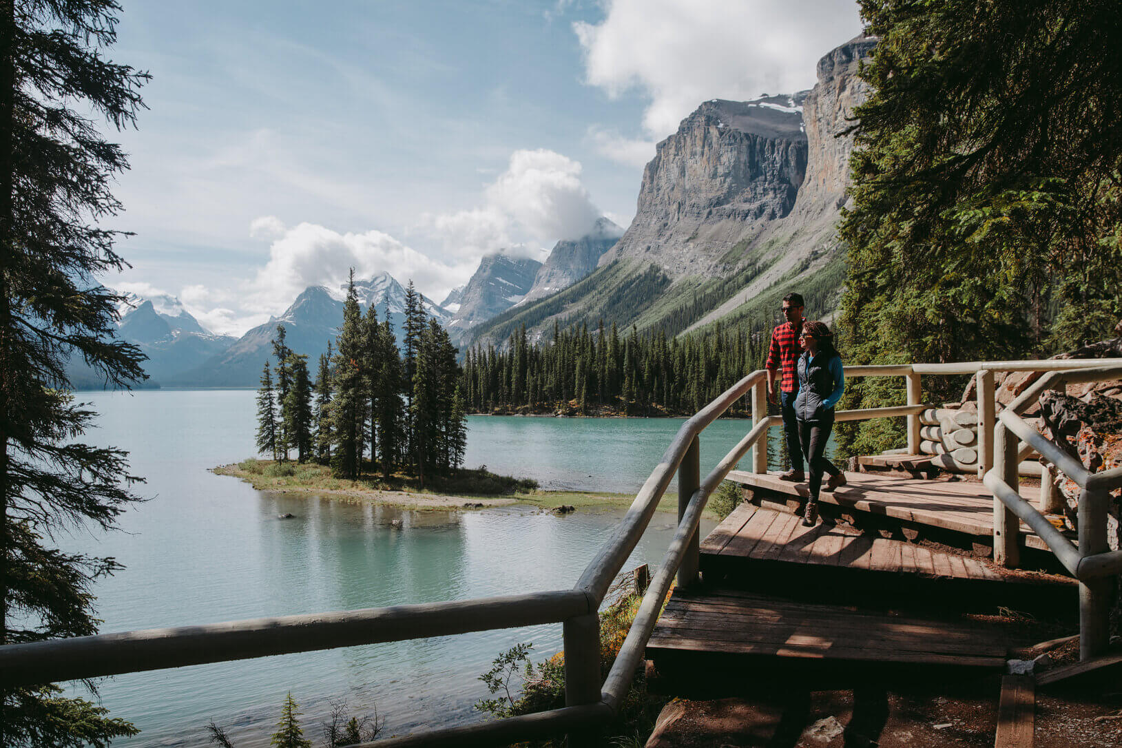 two hikers on the boardwalk at maligne lake