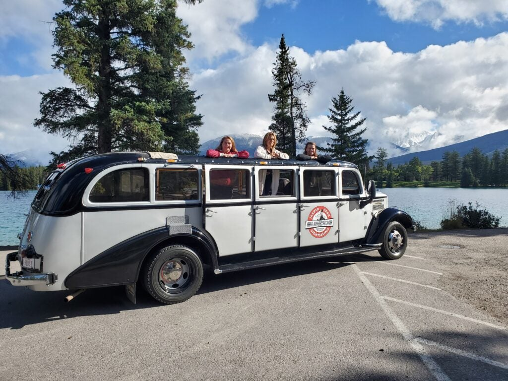 Three visitors stand out of the sun roof on the historic Jammer vehicle in Jasper National Park